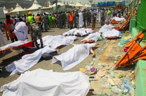 Saudi emergency personnel and Hajj pilgrims stand near bodies covered in sheets where at least 450 were killed and hundreds wounded in a stampede in Mina, near the holy city of Mecca, at the annual hajj in Saudi Arabia on September 24, 2015 (AFP Photo/)