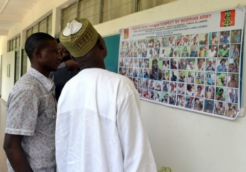 People look at a poster in Maiduguri on October 28, 2015 displaying one hundred Boko Haram suspects declared wanted by the Nigerian army