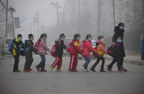 Schoolchildren cross the street in Jinan, in east China's Shandong province on December 24, 2015 amid heavy air pollution (AFP Photo)