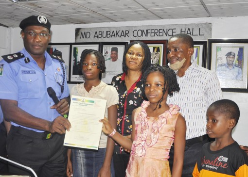L-R: Lagos State Commissioner of Police, Fatai Owoseni, late Comfort Idongesit Udoh's daughter, Mary;  President Women Arise,  Dr. Joe Okey-Odumakin; Comfort's daughter, Blessing; widower of the late Comfort, Mr. Sunday Udoh and Udoh's son, Abraham, during the presentation of scholarship by the police to them in Lagos on Monday,11 Jan., 2016