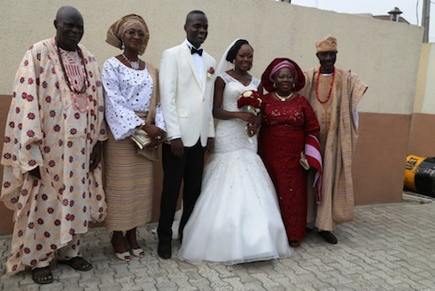Parents of the bride and groom take photograph with the new couple