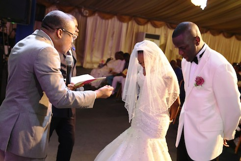 Pastor Tunji Sapara blesses  Adefemi  Onanuga and his wife, Olubukola