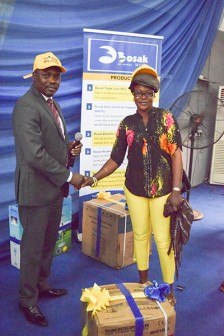 MD-CEO of Bosak Microfinance Bank Limited,Kola Bello at its second Beta Life Saving Promo held at Primrose Events Place, Lagos. With him is Star Prize Winner of the raffle draw, Funke Ekunsanmi.