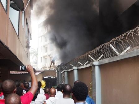 People look on as Samsung showroom/digital centre burns