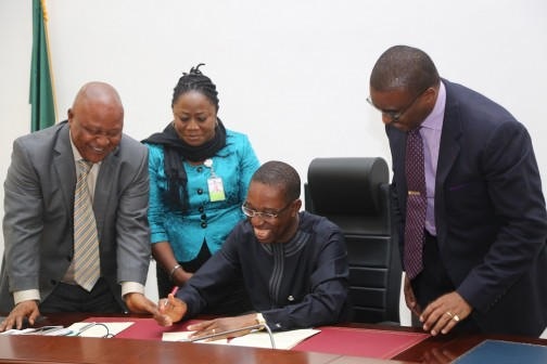 Delta State Governor, Senator Ifeanyi Okowa (sitting); Speaker, State House of Assembly, Rt Hon Monday Igbuya (left); Clerk of the House, Mrs Lyna Ochulor (2nd left) and Commissioner for Finance Mr David Edevbie at the signing of the 2016 Appropriation Bill into law in Asaba.