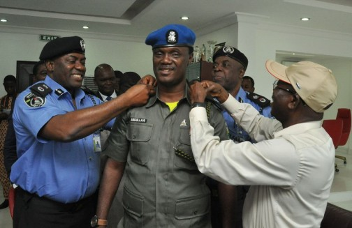 Governor Oshiomhole and the Commissioner of Police, Mr Chris Ezike decorating Mr Ibrahim Abdullahi with his new rank on Thursday, 10 September, 2015