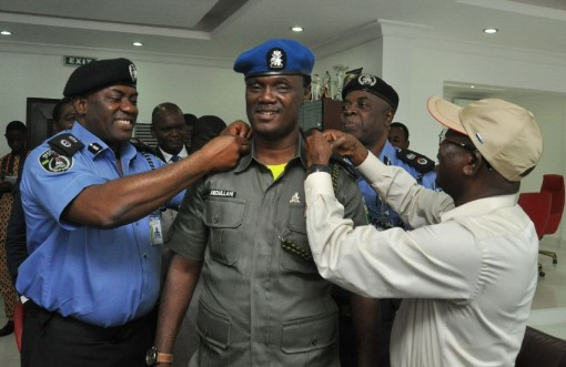 Governor Oshiomhole and the Commissioner of Police, Mr Chris Ezike decorating Mr Ibrahim Abdullahi with his new rank on Thursday, September 10, 2015