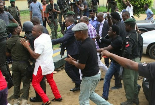 Minister of Transportation, Rotimi Amaechi (in purple and white check shirt) surrounded by security operatives as he arrives the venue