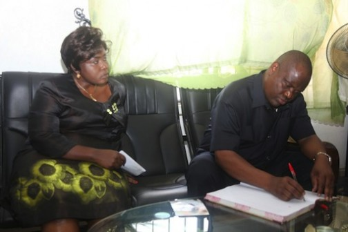 Governor Nyesom Wike signs the condolence book as Rivers State NYSC Coordinator, Mrs Ngozi Nwatarali looks on during  the governor's condolence visit to the state NYSC  headquarters over the death of Samuel Okonta,  corps member killed  during  Rivers rerun elections