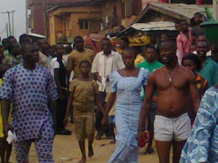 SHOW OF SHAME: Inspector Ibrahim Odufarasin (bare chested and wearing only shorts)  and his  Onyabo Boys on Church Street in Ijora Badia