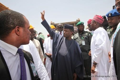 Governor Abdullahi Ganduje (R) looks on as Prof Yemi Osinbajo waves to the crowd