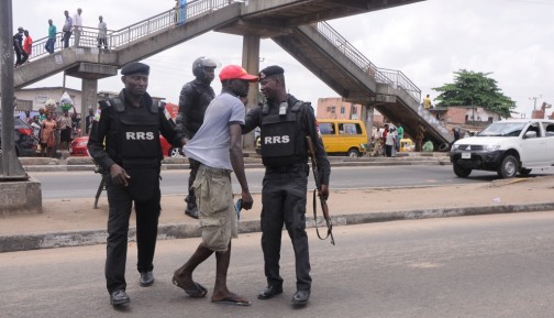 A Pedestrian being apprehended for crossing the expressway at Ketu, Ikorodu Road, Lagos by men of the Rapid Response Squad (RRS), on Monday, April 11, 2016.