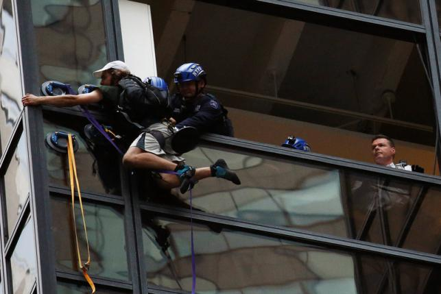 Officers from the NYPD embrace a man to stop him from climbing the outside of Trump Tower in New York
