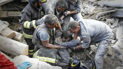 Rescuers bringing out a man from the rubble of his fallen home