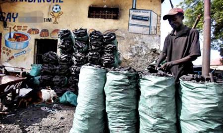 A trader arranges charcoal inside sacks along a street near the