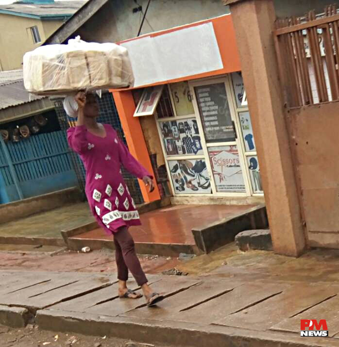 Bread Seller braves rain to hawk @ Ile-Epo.