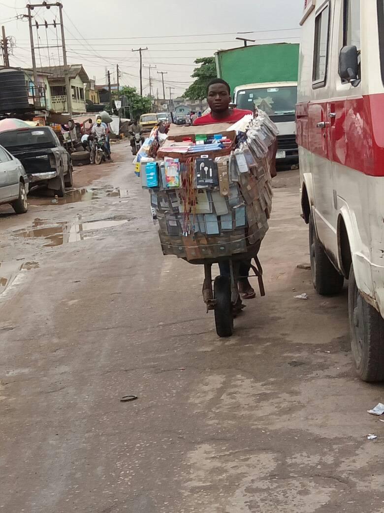 Man pushing cart of phone accessories in Ojuelegba, Lagos