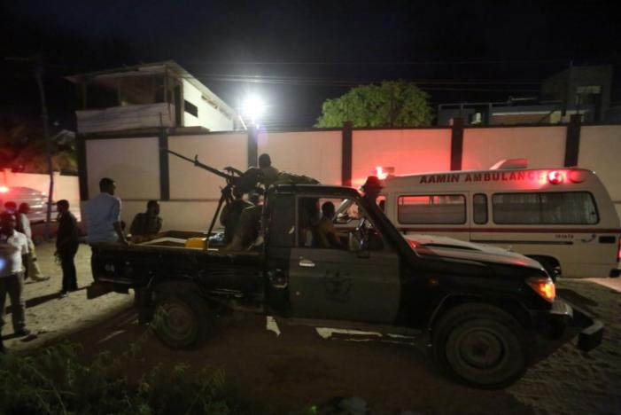 Armed security forces and rescue personnel are seen at the scene of an attack outside an hotel in Mogadishu