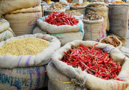 red hot chili pepper and other spices in jute gunny-bags on indian market
