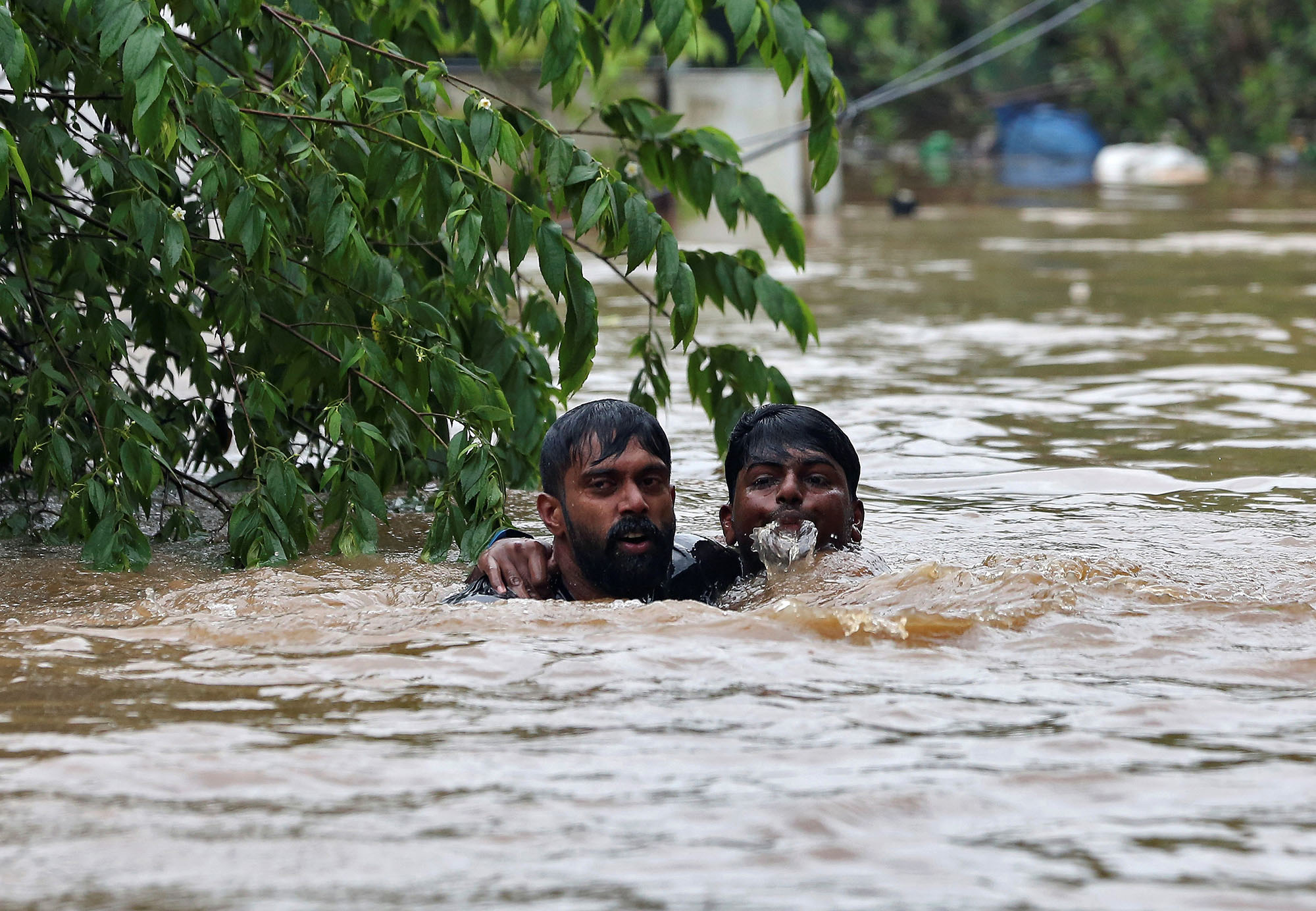 A man rescues a drowning man from a flooded area after the opening of Idamalayr, Cheruthoni and Mullaperiyar dam shutters following heavy rains, on the outskirts of Kochi