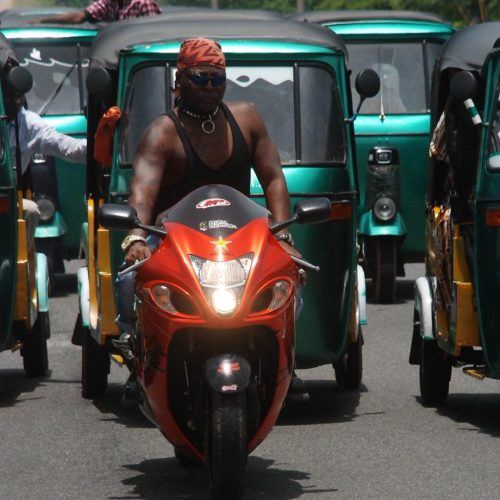 Charly Boy on his power bike with Tricycle riders making up his convoy