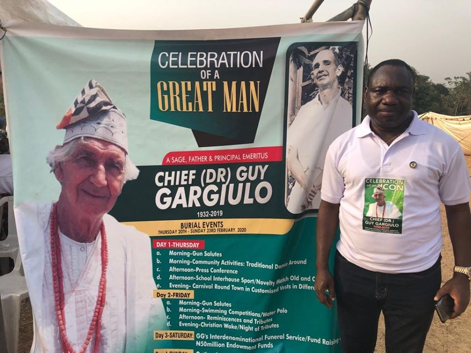 Mr. Gbenga Omotoso standing by the flex banner of his late mentor, Guy Garguilo, in Oke Agbe, Ondo State