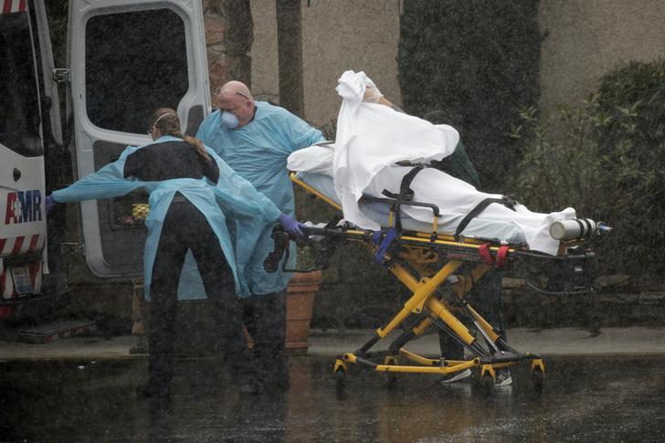 Medics transport a patient through heavy rain into an ambulance at Life Care Center of Kirkland
