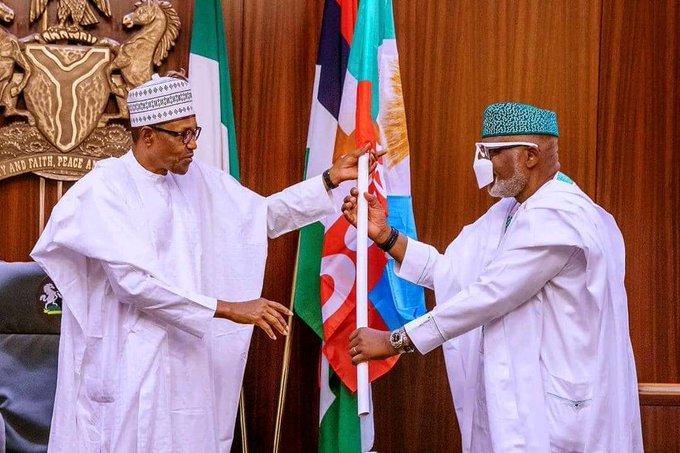 File: Buhari presenting APC flag to Akeredolu last September