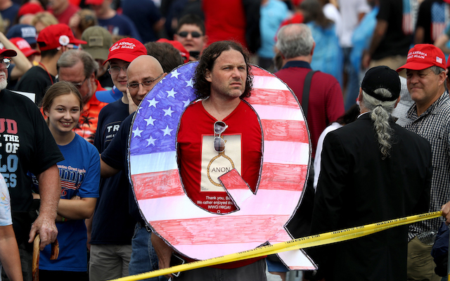 """Image:  David Reinert holds a large """"Q"""" sign while waiting to see Trump"""