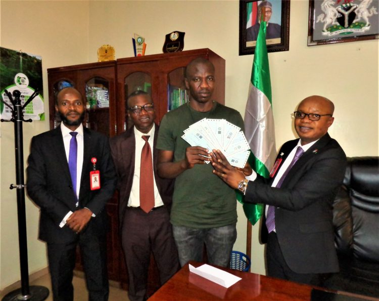 Oshodi Johnson (4th R) Zonal Head, EFCC,Enugu Zonal Office, handing over the recovered cheques to the victim .docx