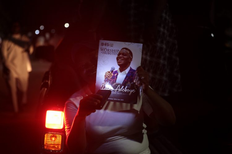 A worshipper with the tribute programme for late Dare Adeboye