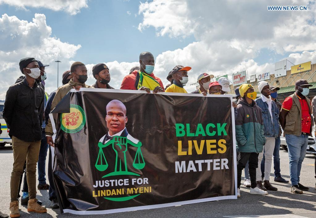 People protest as the remains of the late South African rugby player Lindani Myeni arrived at OR Tambo International Airport in Johannesburg, South Africa, May 1, 2021.