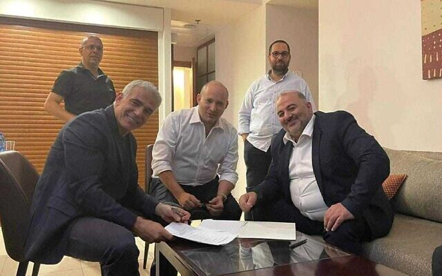 Yesh Atid leader Yair Lapid (L), Yamina leader Naftali Bennett (C) and Ra'am leader Mansour Abbas sign a coalition agreement on June 2, 2021