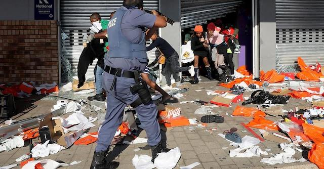 A policeman tries to control looting by Zuma supporters