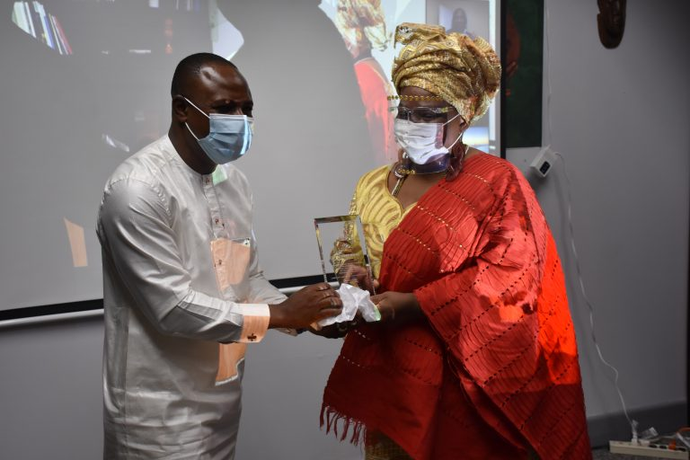 Amb. Gabriel Aduda, presents  a plaque to Ms Joyce Adewumi, President of African Chorus Ensemble for her efforts at promoting Nigeria's culture