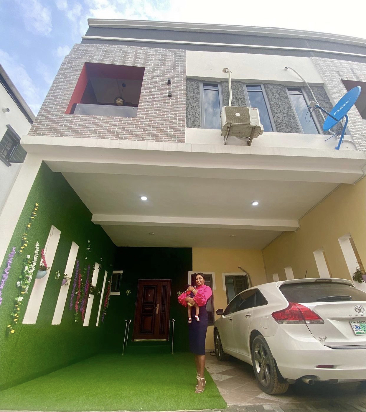 Etinosa Idemudia in front of her new home