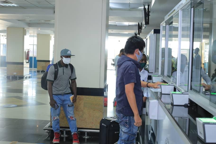 Julius Ssekitoleko behind in a fac cap while being returned to Uganda