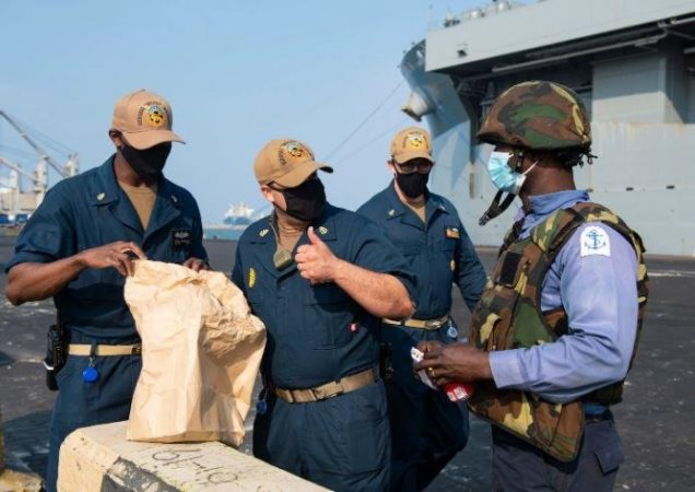 A Nigerian Navy sailor, far right, meets crewmembers of the USS Hershel Woody Williams prior to exercises in the Gulf of Guinea.