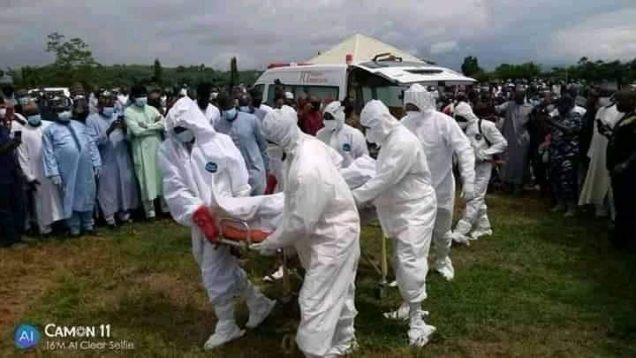 Men in protective suits carry the body of Senator Mantu at the burial ground in Abuja