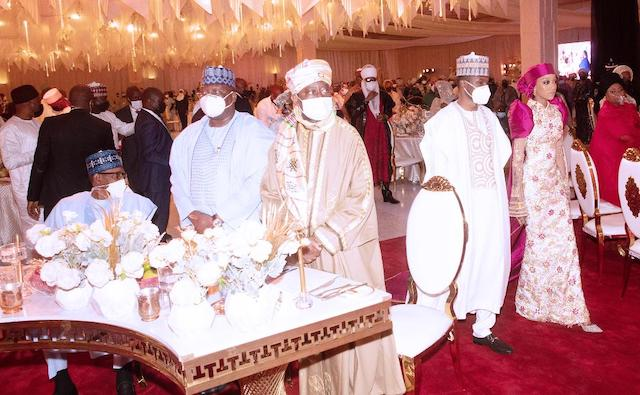 Buhari, sitting left,  watches as his son and his wife walk in