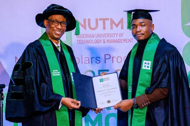 One of the graduating students receives a certificate from Enelamah