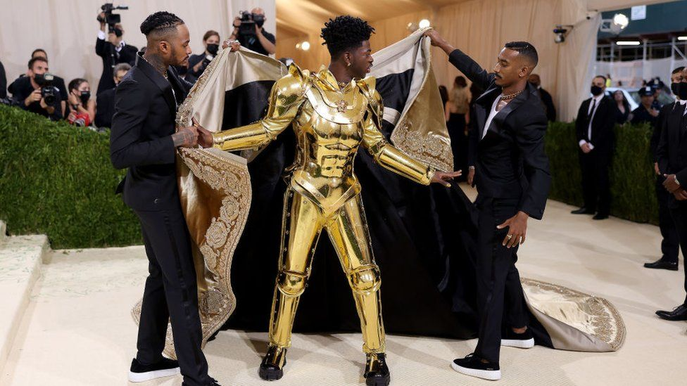 Lil Nas whipped off the robe to reveal a golden suit of Versace armour.